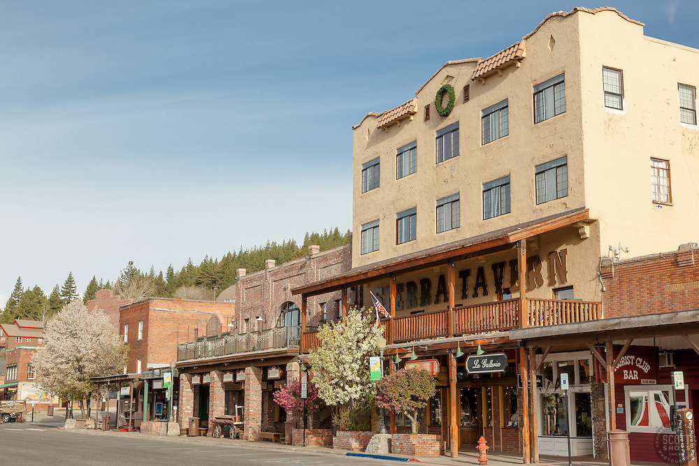 """Downtown Truckee 16"" - Photograph of the Sierra Tavern  and other buildings in historic Downtown Truckee, California with blossoming cherry tree and crabapple trees in the foreground."