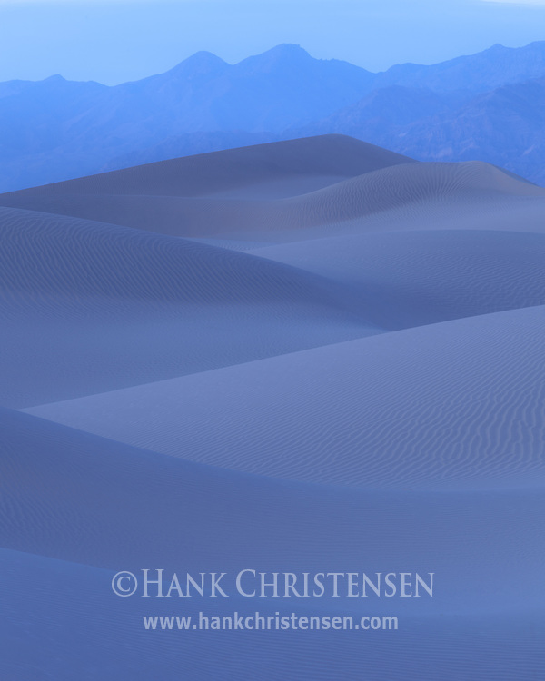 In the blue shades of twilight, smooth dunes stretch to distant mountains, Death Valley National Park