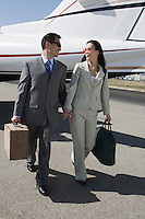 Mid-adult Asian business couple walking in front of airplane.