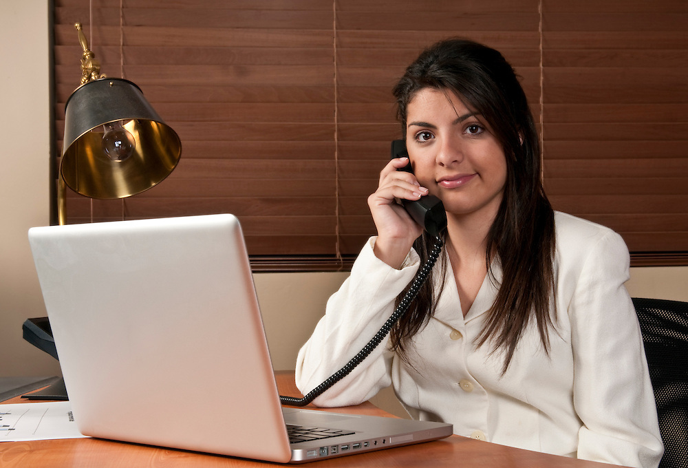 Young woman working in a small office and talking by phone.