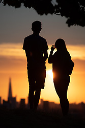 © Licensed to London News Pictures. 24/07/2018. London, UK. A couple watch the sunset over London's skyline, after temperatures in the South East of England reached over 30 degrees celsius today. Temperatures are set to rise up to 35 degrees on Thursday, as the UK experiences a prolonged heatwave. Photo credit : Tom Nicholson/LNP