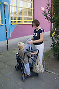 Mom ages 28 and 3 packing stroller outside Rainbow Preschool Teczowe Przedszkole Balucki District Lodz Central Poland