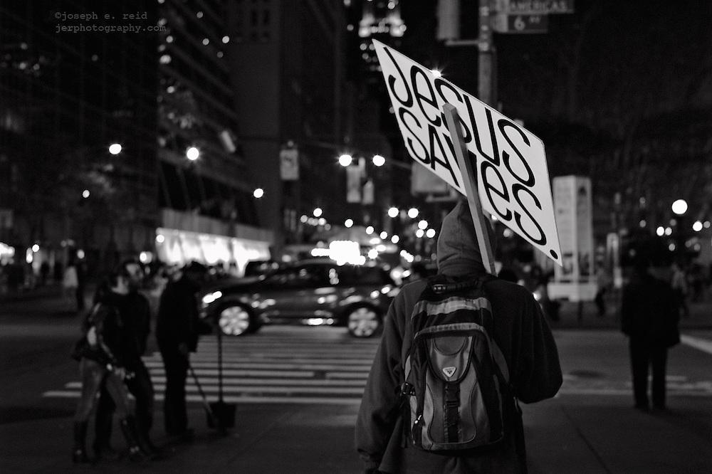 Man with Jesus Saves sign walking along 42nd Street at night, New York, NY, US
