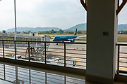 A Vietnam Airlines jet aircraft approaches the jet bridge at the Luang Prabang Airport,  Luang Prabang, Laos.