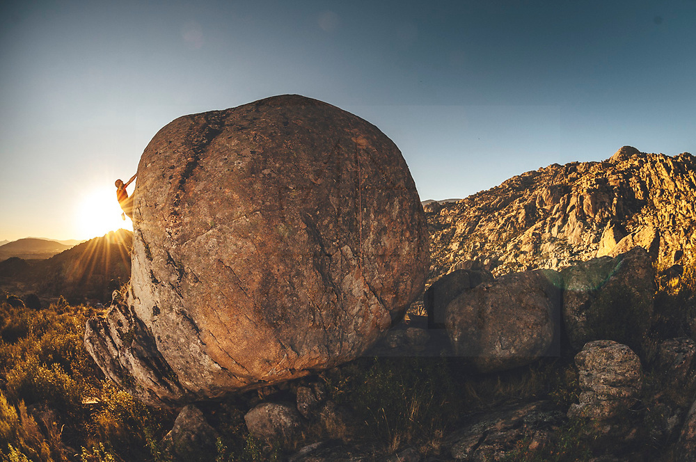 Climber climbing a rocky boulder problem in the middle of the forest at sunset with lensflare