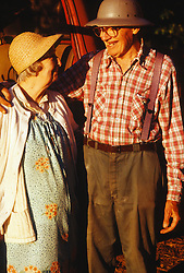 Elderly couple in farm clothes embracing and smiling
