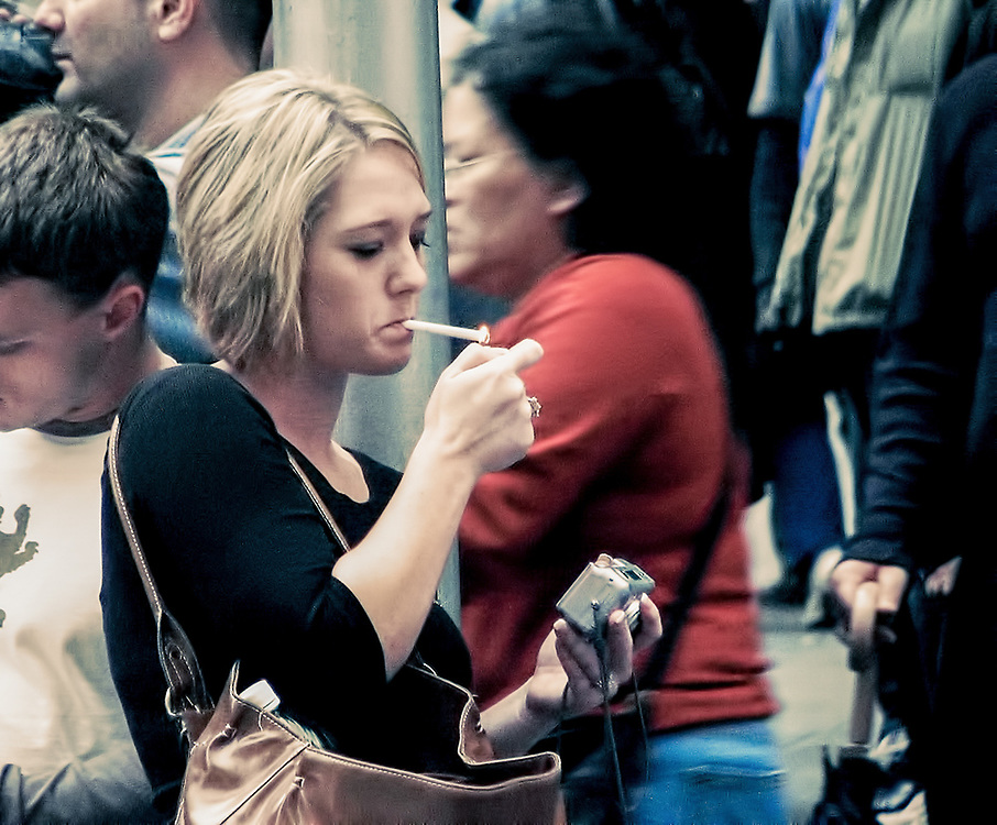 Blond girl lighting up cigarette on crowded ny street. NYC 2006