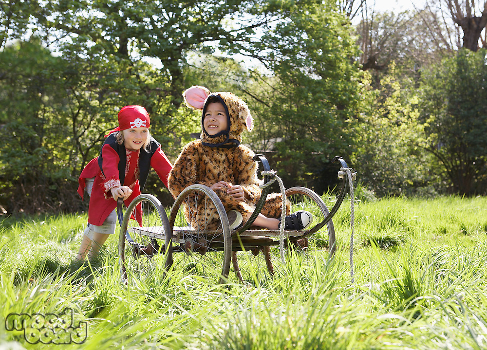 Young boy (7-9) in pirate costume pushing boy (5-6) in cart in jaguar costume smiling