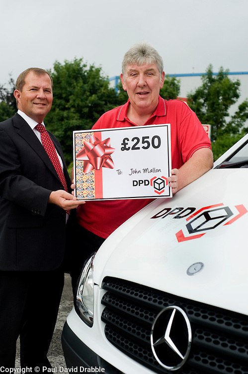 DPD Owner Driver Franchisee John Mallon (right) receives a gift voucher for £250 from Regional Manager Steve Church  at the DPD distribution centre  at Thorncliffe Chapeltown Sheffield 14  July 2010 .Images © Paul David Drabble.