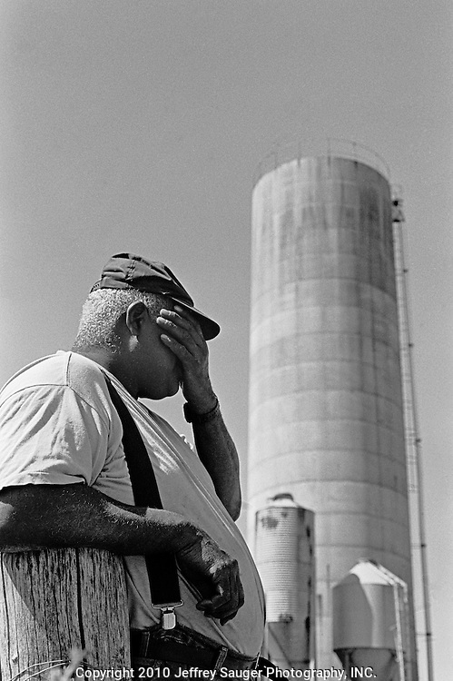 "BIDWELL, OHIO - October 1999: James Howard wipes his brow after cutting tobacco in Bidwell, Ohio, in October 1999. To help ends meet, James drives a school bus full-time, raises hogs and with his brother Bill Howard raises hay and tobacco. In 1974, Bill Howard bought his silo, feed bunk, and drag chain for $25,000. Today it would cost about $65,000. ""Money ain't everything, but, it kind of helps to have some. If I die they ain't gonna fight over my money."" Howard said. (Photo by Jeffrey Sauger)"