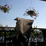 A gentleman reads the newspaper in the early boring light in a cafe over looking the Saigon River, Ho Chi Minh City, Vietnam. 3rd March 2012. Photo Tim Clayton