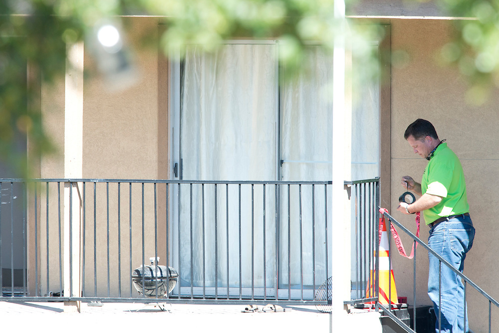 A man tapes off a neighbors porch as a haz-mat crew prepares to enter the Ivy Apartments where Thomas E. Duncan, the first confirmed Ebola virus patient in the United States, was staying with family in Dallas, Texas on October 3, 2014. Duncan is now being treated at Texas Health Presbyterian Hospital Dallas while members of his family have been isolated in the apartment. (Cooper Neill for The New York Times)