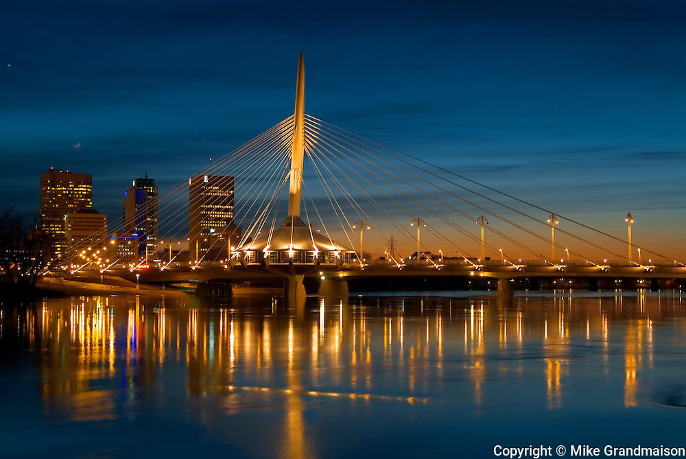 Esplanade Riel Bridge, the Red River and the Winnipeg skyline at dusk<br /> Winnipeg<br /> Manitoba<br /> Canada