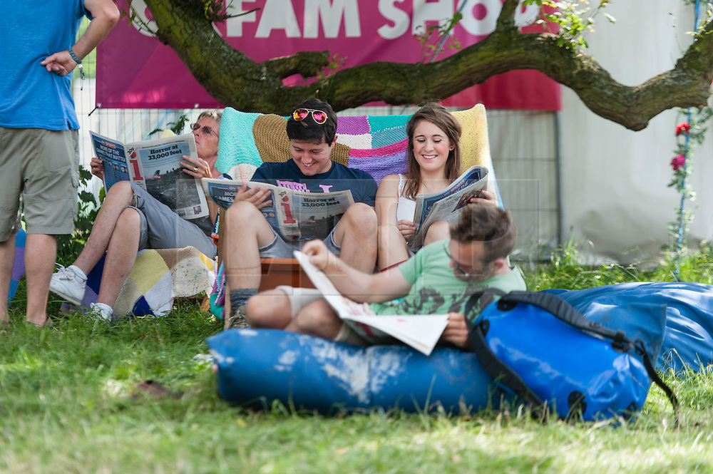 © Licensed to London News Pictures. 18/07/2014. Southwold, UK.   Festival goers relax from the hot sun in the shade at  Latitude Festival 2014 Day 1. Today is expected to be the hottest day of the year with temperatures forecast to reach 32 degrees centigrade.   Latitude is an British annual music festival.  Photo credit : Richard Isaac/LNP