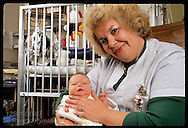 Nurse Judy Compton cradles heart-surgery baby in neonatal intensive care unit of St Louis Children's Hospital; Missouri