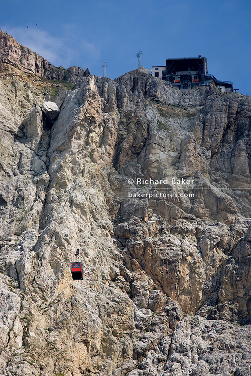 From Passo Falzarega (Pass), a cable car gondola ascends the rock face of Lagazuoi  (3,244 m), a Dolomites mountain in south Tyrol, Italy.  One of two gondolas rises to the Lagazuoi (2,835), which was the object of heavy combat in World War I. Lagazuoi is a mountain in the Dolomites of northern Italy, lying at an altitude of 2,835 metres (9,301 ft), about 18 kilometres (11 mi) southwest by road from Cortina d'Ampezzo in the Veneto Region. It is accessible by cable car and contains the Refugio Lagazuoi, a mountain refuge situated beyond the northwest corner of Cima del Lago. The mountain range is well known for its wartime tunnels.