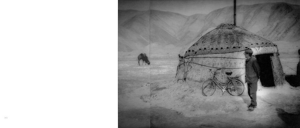 Kyrgyz herdsman watches his camels from outside his yurt, beside Karakuli Lake.  Pamir Mountains, Chinese Turkestan.  2002