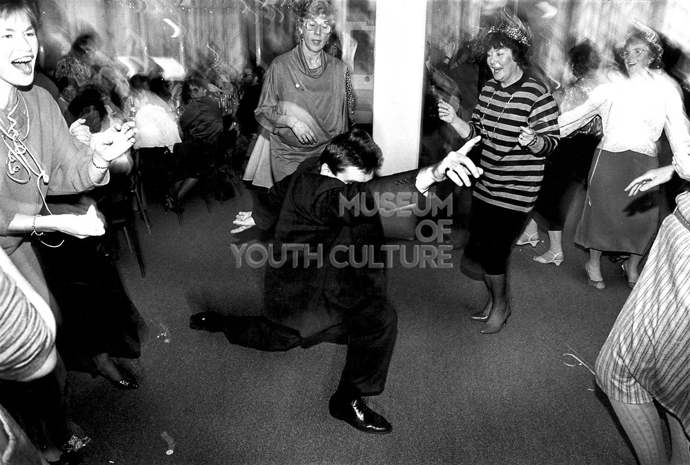 A man strikes a pose dancing in the middle of a group of older women at an office christmas party Newport Wales c.1990.