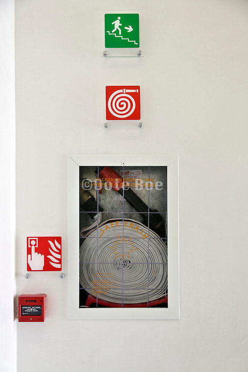emergency exit signs and fire hose in public building Venice Italy