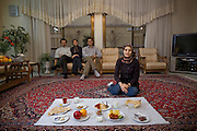 Atefeh Fotowat, a high school student and aspiring fashion designer with her typical day's worth of food at her home in the city of Isfahan, Iran.  (From the book What I Eat: Around the World in 80 Diets.)  The caloric value of her typical day's worth of food in December was 2400 kcals. She is 17 years of age; 5 feet, 4.5 inches tall; and 121 pounds. Her father, a renowned miniaturist painter, is seated on the couch, along with her mother and her brother, a university student. Together, they exemplify the educated Iranian upper middle class in Isfahan, Iran's third largest city, famous for art and Islamic architecture. Atefeh's relaxed repose and her attire, combining jeans and headscarf, show her ease with foreigners yet respect for tradition. She aspires to turn her fashion designing avocation into a vocation by becoming a designer after college.  MODEL RELEASED.