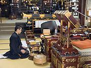 Buddhist priest praying in temple Tokyo Japan