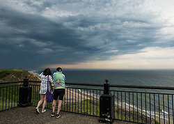 © Licensed to London News Pictures.01/07/15<br /> Saltburn by the Sea, UK. <br /> <br /> A couple stand and watch as a brooding thunderstorm passes over Teesside and heads out into the north sea after what has been one of the hottest days so far this year.<br /> <br /> Photo credit : Ian Forsyth/LNP