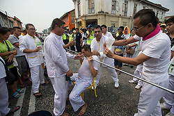 © Licensed to London News Pictures. 18/10/2015 Batu Gajah, Perak, Malaysia. Devotees prepare to remove a metal pole speared through a devotee's mouth at Sam Wong Kong temple during the Nine Emperor Gods Festival celebration in Batu Gajah, Malaysia, Sunday, Oct. 18, 2015. Photo credit : Sang Tan/LNP