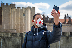 © Licensed to London News Pictures. 16/03/2020. London, UK. A man wearing a face mask in front of a very quiet and empty Tower of London today which is normally busy with tourists at this time (11:55am). New cases and fatalities resulting from the COVID-19 strain of the Coronavirus continue to be reported daily in the UK with major sporting fixtures cancelled and people advised to stay at home if they have a cough and high temperature. Photo credit: Vickie Flores/LNP