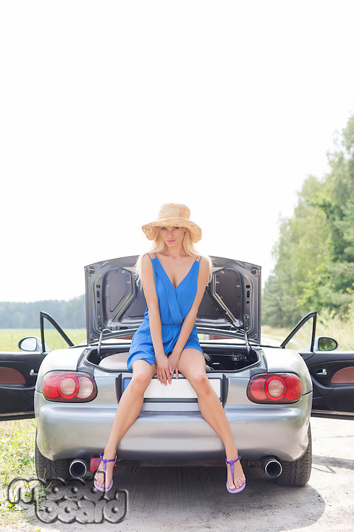 Full length portrait of woman sitting on convertible trunk against clear sky