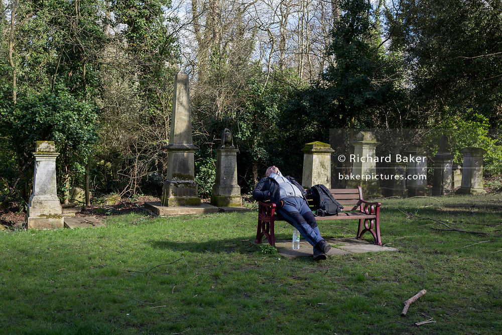 A male visitor sleeps with his head back while sitting in front of Victorian graves and memorials in south London's in south London's Nunhead Cemetery, on 1st march 2020, in London, England. Nunhead is of the great Victorian Cemeteries of London. Consecrated in 1840, it is one of the seven great Victorian cemeteries established in a ring around the outskirts of London, its 52-acre site near Peckham is the final resting place for many members of Victorian society: From music hall artists, inventors, WW1, and soldiers who survived the battles of Waterloo and Trafalgar.