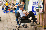 09 APRIL 2012 - HANOI, VIETNAM:  A barber cuts a client's hair at his street stall  in Hanoi, the capital of Vietnam. Although woman go to western style beauty parlors for hair care, many men get their hair cut at a street side barbers. Hanoi, established in 1010 AD, is one of the oldest permanent cities in Southeast Asia. PHOTO BY JACK KURTZ
