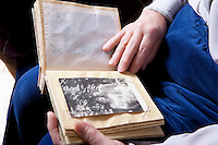 Elderly lady sits looking at photograph album