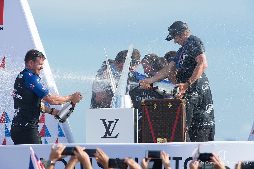 Americas's Cup Village, Bermuda 12th June 2017. Emirates Team New Zealand helmsman Peter Burling and cyclor Joe Sullivan spray each other with champagne on stage after winning the Louis Vuitton America's Cup Challenger series.
