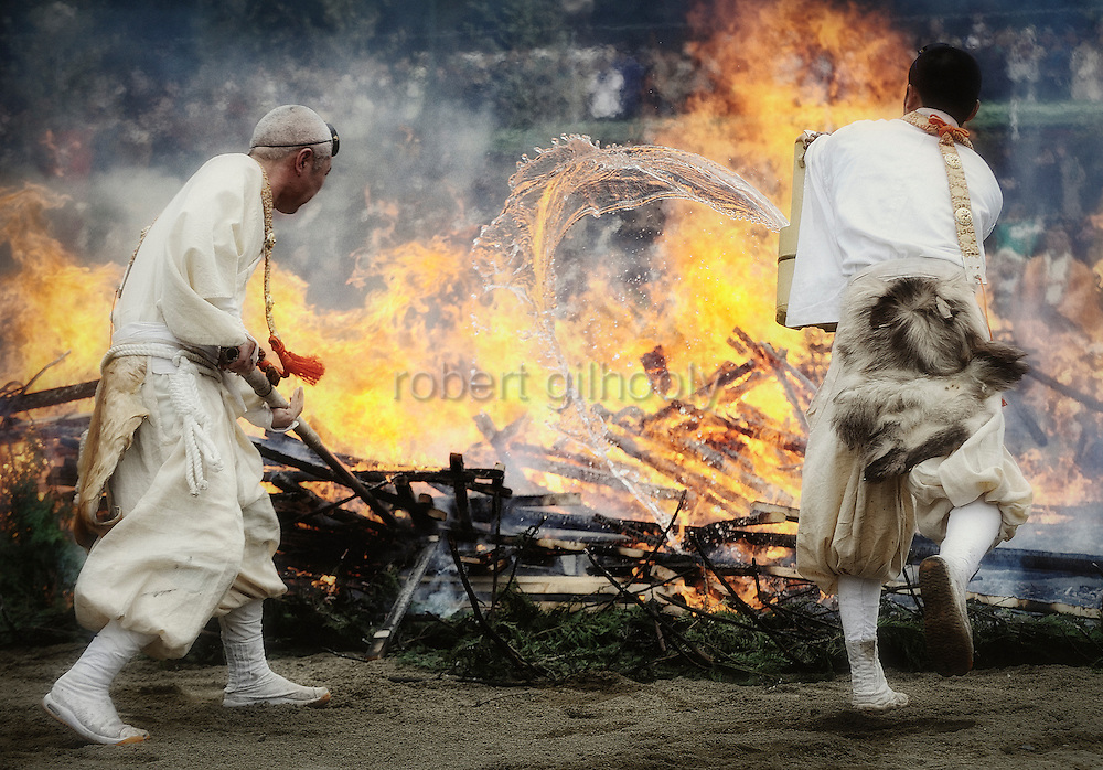 Buddhist monks throw water to help calm the flames just prior to a ritual in which participants walk barefoot across burning embers during a purification ceremony in Takao, west of Tokyo, Japan on Sunday 09 March  2009.