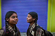 Before lessons begin, Poonam, 12, (left) and her sister Jyoti, 13, (right) are standing on the street facing the cozy, private school they regularly attend since 2011, located by their newly built home in Oriya Basti, one of the water-contaminated colonies in Bhopal, central India, near the abandoned Union Carbide (now DOW Chemical) industrial complex, site of the infamous '1984 Gas Disaster'.