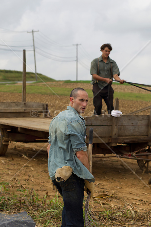 two male farmers in the field and on a wagon in Lancaster, PA