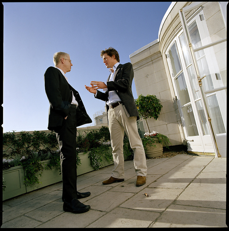 British actor, Hugh Grant (right), talks to Richard Curtis, Director of his latest movie, 'Love Actually'..Photographed on a terrace of The Dorchester Hotel, in London.
