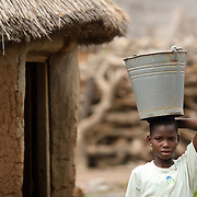 "Mariam Alhassan, 11, carries an empty bucket on her head as she prepares to head out to fetch water with other girls after coming home from school in the village of Ying, in the Savelugu-Nanton district, northern Ghana on Monday June 4, 2007. ""I saw some other children go to school,"" she recalls, ""but my father said we had no money for me to go. I cried and he agreed to send me."" Before heading to school, Mariam I helps her mother at home by sweeping the floor, cooking, fetching water and firewood.When her father died a few years back, her older brother promised to keep her at school.."