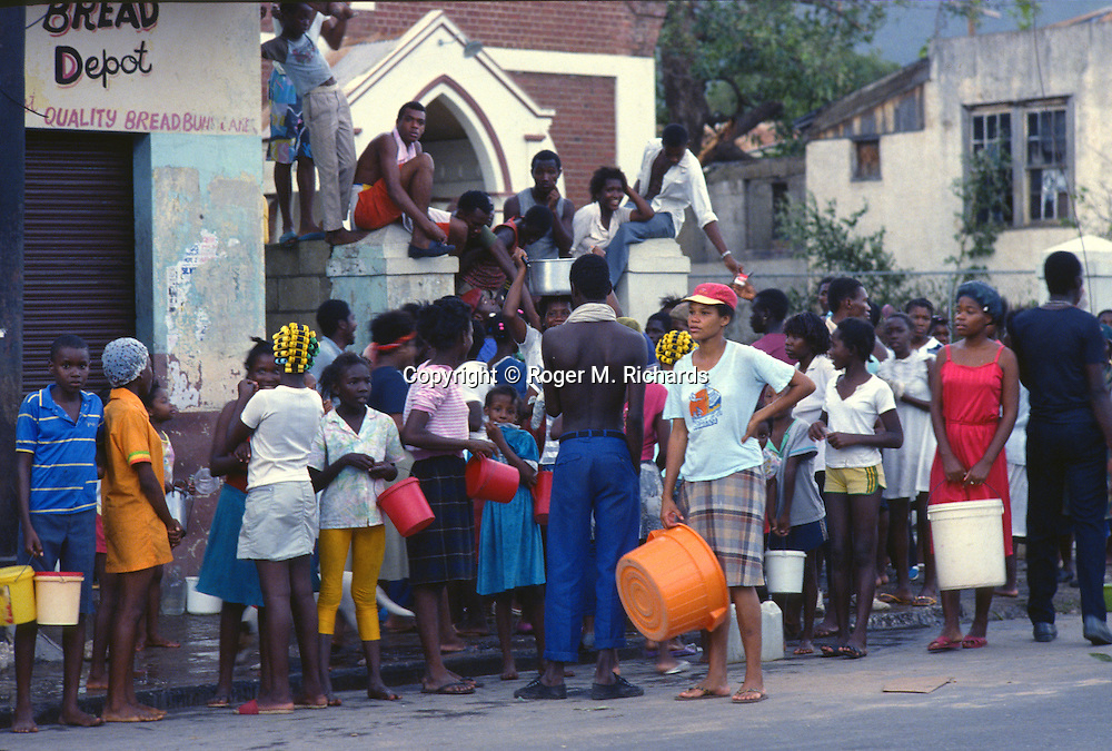 In September 1988 Kingston residents line up for drinking water after Hurricane Gilbert hit Jamaica. By the time the destruction had stopped, 45 people were dead and over 500,000 left homeless. Agriculture was devastated, with US$50 million in damage to coffee, sugar cane, banana and other crops. Looting was widespread, particularly in Kingston. Foreign aid of about US$125 million form the USA alone poured into the stricken island. The tourist parts of the island were returned to normal with remarkable speed, but others took much longer to recover from the devastation.