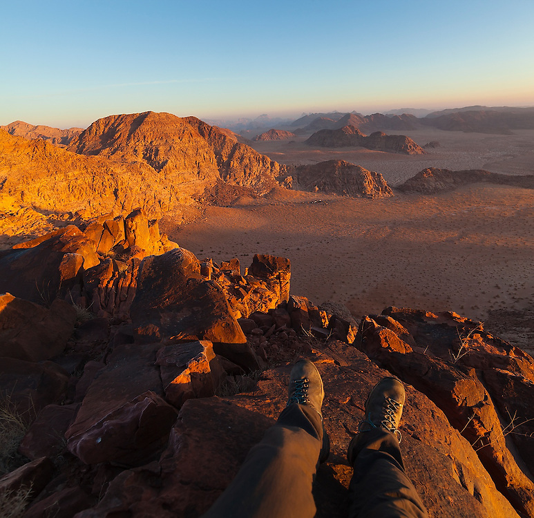 Ethan Welty sits on a high ridge at sunrise looking down to the remote encampment of his Bedouin hosts and the mountains beyond in Wadi Rum, Jordan.