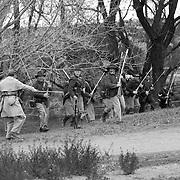 Union forces (5th U.S. Infantry regiment) spring into position from a hiding spot to meet advancing confederate forces at a reenactment of the battle of Glorieta pass.