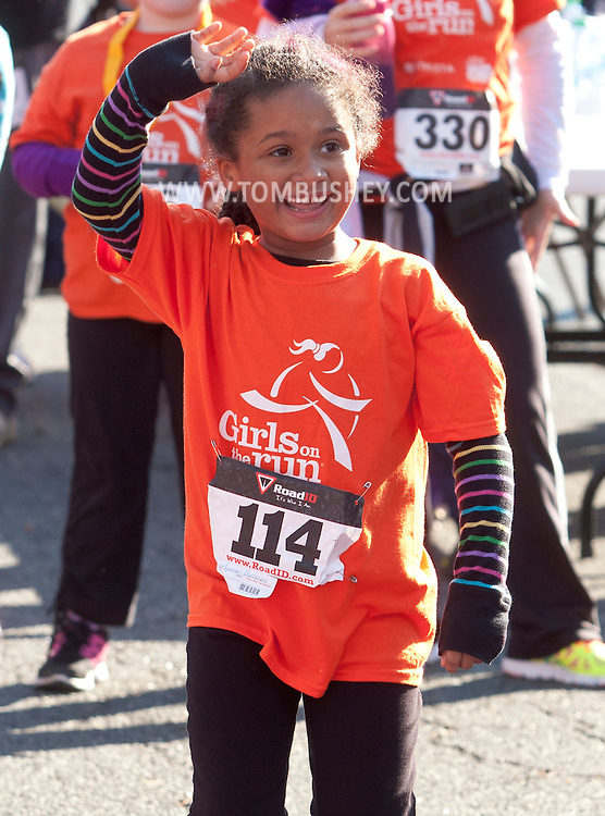 Cornwall-on-Hudson, New York - A girl in the Girls on the Run Hudson Valley program smiles and waves after finishing the Cornwall Lions Club Fall Harvest Race 5K on Nov. 10, 2013. Girls on the Run is a national program with a mission of helping girls to be joyful, healthy and confident using an experience-based curriculum which creatively integrates running.