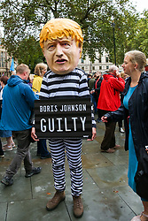© Licensed to London News Pictures. 24/09/2019. London, UK. A protesters wearing prisoner's outfit and Boris Johnson's face mask outside Supreme Court in London after the court ruled that the Prime Minister Boris Johnson's decision to prorogue Parliament is unlawful. Last week the court heard an appeal in the multiple legal challenges against the Prime Minister Boris Johnson's decision to prorogue Parliament ahead of a Queen's speech on 14 October.  Photo credit: Dinendra Haria/LNP