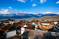 A view over a small village in Dali, China, with surrounding homes and the Cangshan Mountains in the background.