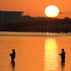 Fisherrmen along the Dunedin Causeway in Dunedin, Florida at sunrise.