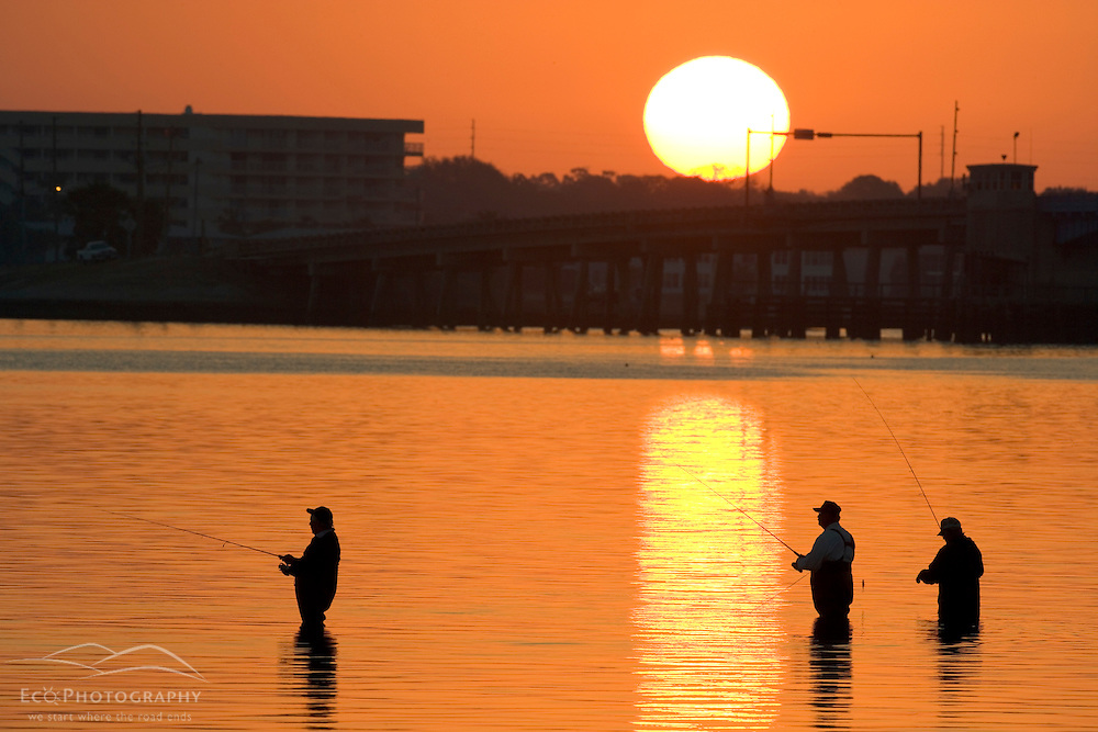 Fisherrmen along the Dunedin Causeway in Dunedin, Florida at sunrise.