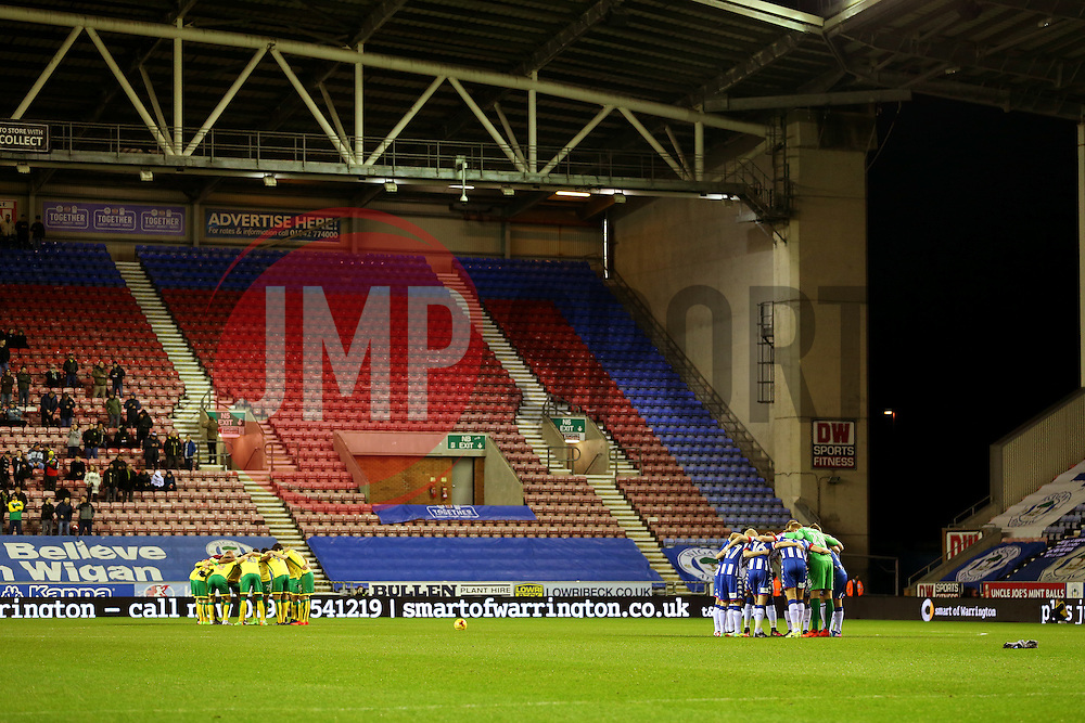 Wigan Athletic and Norwich City players huddle before kick off in front of an sparsely populated away stand - Mandatory by-line: Matt McNulty/JMP - 07/02/2017 - FOOTBALL - DW Stadium - Wigan, England - Wigan Athletic v Norwich City - Sky Bet Championship