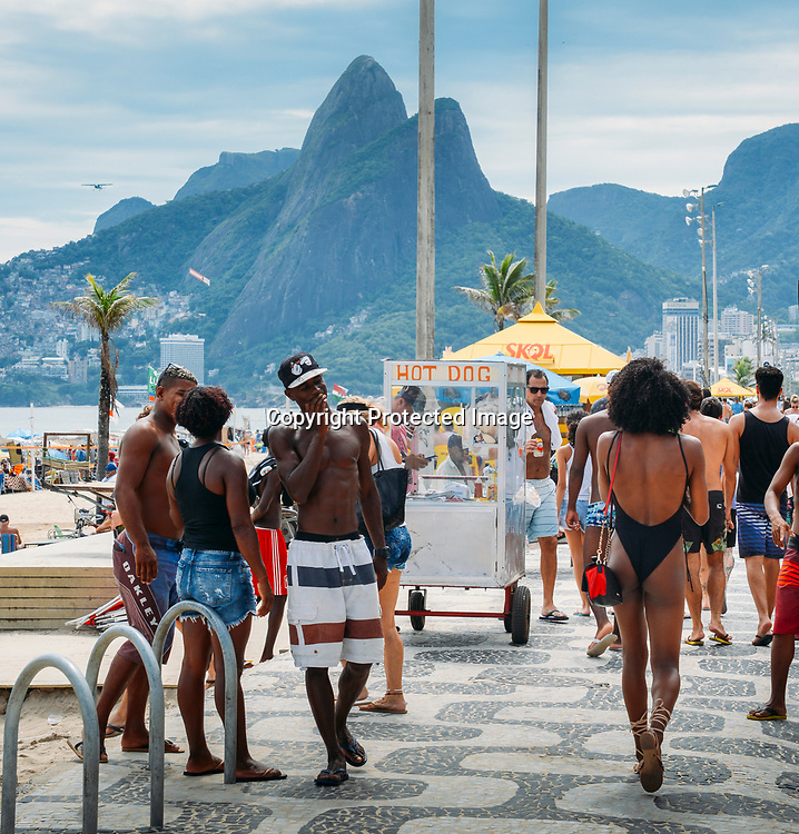 Rio de Janeiro, Brazil - Jan 6, 2018: Man checks out beautiful Afro-Brazilian woman walking down the promenade at Ipanema Beach, Rio de Janeiro, Brazil