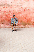 Man rests by wall in the medina of Marrakesh, Morocco.