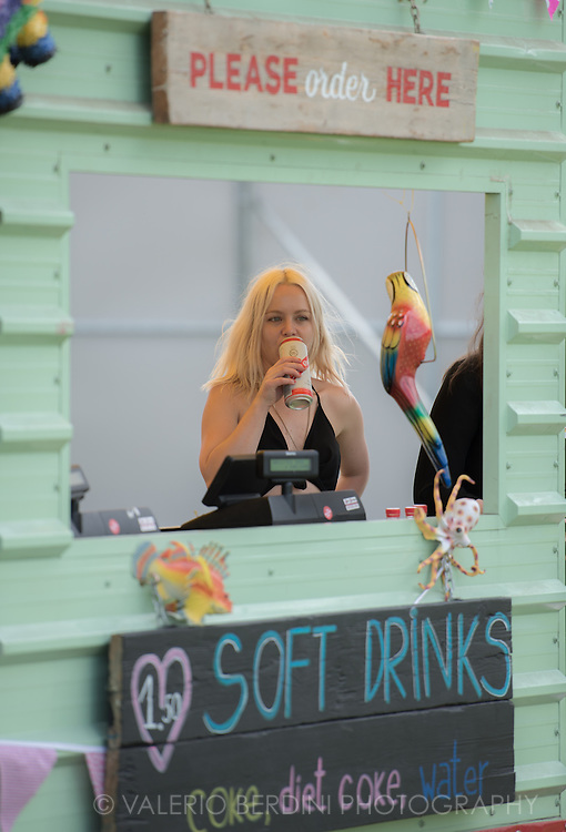 Girl having a Red Stripe beer on her soft drink stalls.